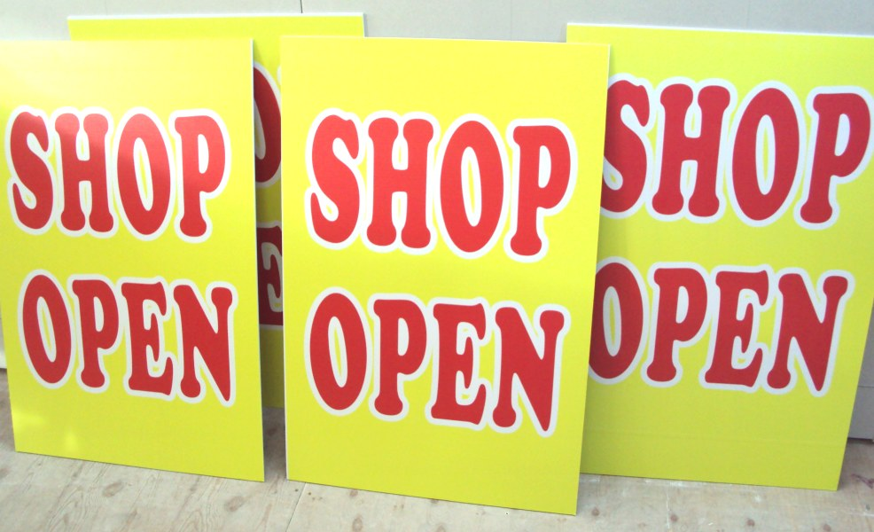 yellow signs with text saying  shop open