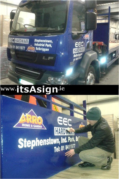 signmakers adding signs to blue lorry